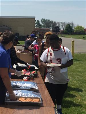 Students at BBQ school-wide celebration  getting lunch
