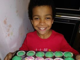 Boy holds tray of cupcakes